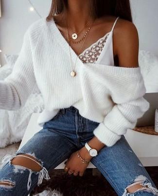 Как и с чем носить: белый вязаный свободный свитер, белая кружевная майка, синие рваные джинсы, золотая подвеска