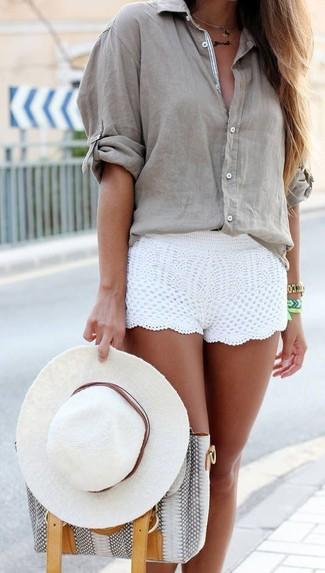 Как и с чем носить: серая блуза на пуговицах, белые шорты крючком, серая кожаная большая сумка со змеиным рисунком, белая шляпа