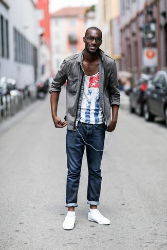 Как и с чем носить: серая куртка в стиле милитари, бело-красно-синяя футболка с круглым вырезом с принтом, темно-синие джинсы, белые кожаные низкие кеды