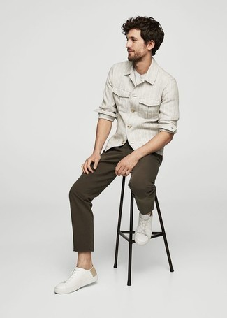 С чем носить белые кожаные низкие кеды мужчине: Сочетание серой рубашки с длинным рукавом в вертикальную полоску и темно-коричневых брюк чинос поможет подчеркнуть твой индивидуальный стиль и выгодно выделиться из серой массы. В тандеме с этим луком наиболее уместно будут смотреться белые кожаные низкие кеды.