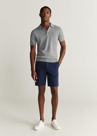 Модные мужские луки 2020 фото в стиле кэжуал: Серая футболка-поло будет выглядеть прекрасно в сочетании с темно-синими шортами. Очень недурно здесь смотрятся белые кожаные низкие кеды.