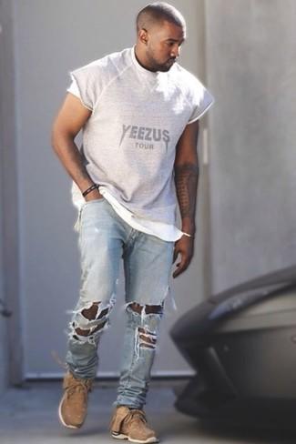 Как Kanye West носит Серая футболка с круглым вырезом с принтом, Голубые рваные джинсы, Светло-коричневые кроссовки