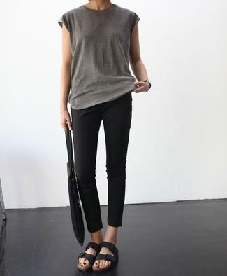 Как и с чем носить: серая футболка с круглым вырезом, черные узкие брюки, черные кожаные сандалии на плоской подошве, черная большая сумка из плотной ткани
