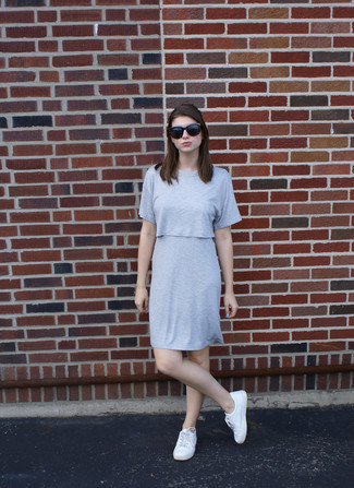 Как и с чем носить: серое платье прямого кроя, белые низкие кеды, черные солнцезащитные очки