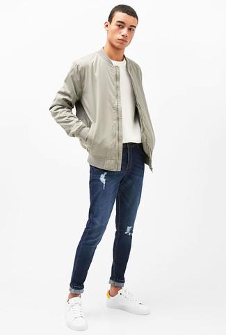 Как и с чем носить: серый бомбер, белый свитер с круглым вырезом, темно-синие рваные джинсы, белые кожаные низкие кеды