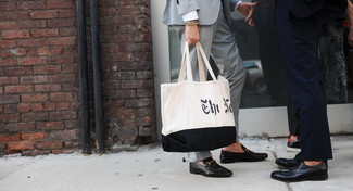 Как и с чем носить: серый костюм, черные кожаные лоферы, бело-черная большая сумка из плотной ткани с принтом