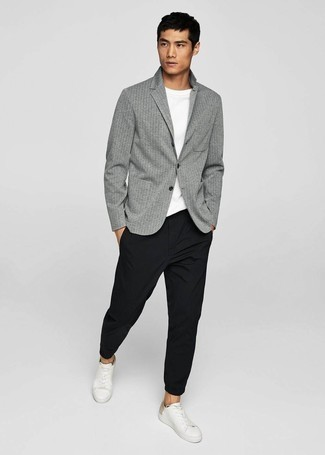 Мужские луки: Серый пиджак в вертикальную полоску и черные брюки чинос — must have вещи в гардеробе мужчин с чувством стиля. Этот ансамбль стильно завершат белые кожаные низкие кеды.