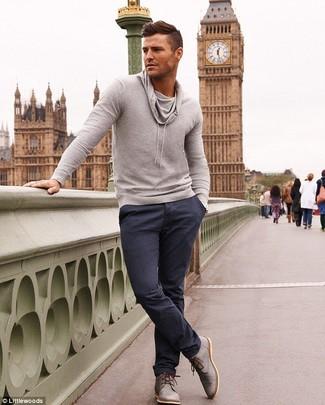 Собираясь в кино или демократичное кафе, обрати внимание на сочетание серого свитера с хомутом и темно-синих брюк чинос. Что касается обуви, неплохо дополнят образ серые кожаные дезерты.