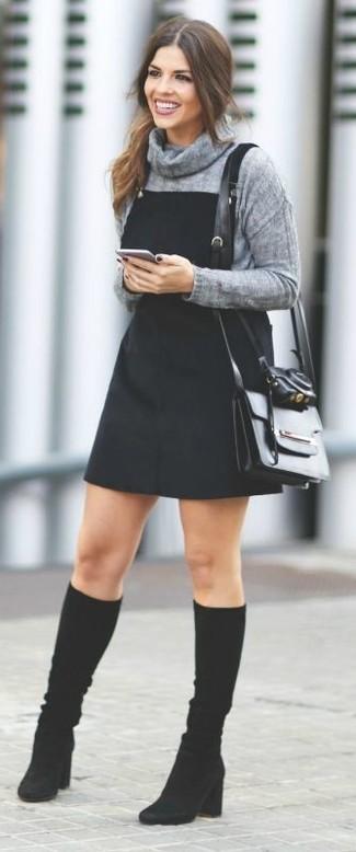 Как и с чем носить: серый свитер с хомутом, черный джинсовый сарафан, черные замшевые сапоги, черная кожаная сумка через плечо