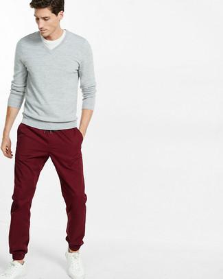 Как и с чем носить: серый свитер с v-образным вырезом, белая футболка с круглым вырезом, темно-красные брюки чинос, белые кожаные низкие кеды