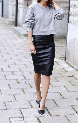 Серый свитшот и черная кожаная юбка-карандаш будут гармонично смотреться в модном гардеробе самых привередливых красавиц. И почему бы не добавить в этот образ элегантности с помощью черных кожаных туфель?