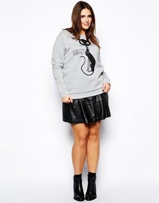 Как и с чем носить: серый свитшот с принтом, черная кожаная короткая юбка-солнце, черные кожаные ботильоны, черные носки