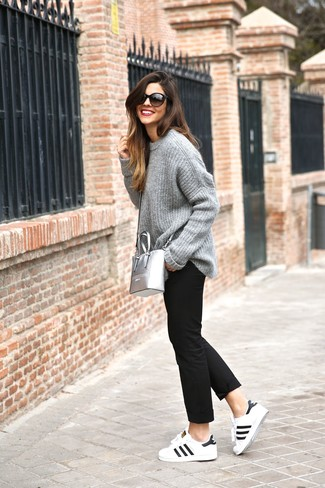 Как и с чем носить: серый вязаный свободный свитер, черные брюки чинос, бело-черные кожаные низкие кеды, серебряная кожаная сумка через плечо