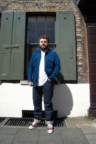 Красные низкие кеды из плотной ткани: с чем носить и как сочетать мужчине: Сочетание синей куртки-рубашки и темно-синих джинсов позволит создать стильный мужской лук. Чтобы образ не получился слишком отполированным, можешь завершить его красными низкими кедами из плотной ткани.