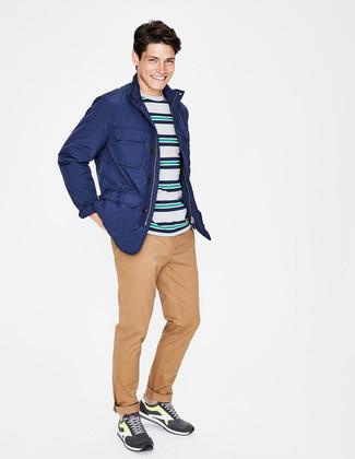 Как и с чем носить: синяя полевая куртка, разноцветная футболка с круглым вырезом в горизонтальную полоску, светло-коричневые брюки чинос, темно-серые кроссовки