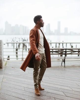 С чем носить коричневые замшевые ботинки челси мужчине: Составив образ из табачного длинного пальто и оливковых брюк чинос, получим подходящий мужской образ для неофициальных встреч после работы. Если тебе нравится смешивать в своих образах разные стили, на ноги можно надеть коричневые замшевые ботинки челси.