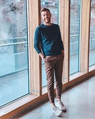 Модные мужские луки 2020 фото: Темно-бирюзовый свитер с круглым вырезом в сочетании с коричневыми брюками чинос поможет выразить твою индивидуальность. Такой образ несложно приспособить к повседневным реалиям, если дополнить его серыми низкими кедами.