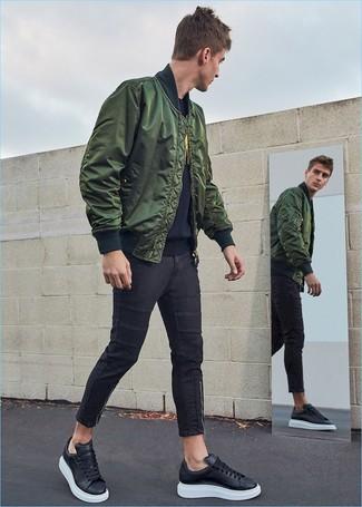 Черные зауженные джинсы: с чем носить и как сочетать мужчине: Темно-зеленый бомбер в сочетании с черными зауженными джинсами не прекращает импонировать стильным джентльменам. В сочетании с этим образом наиболее выигрышно выглядят черные кожаные низкие кеды.