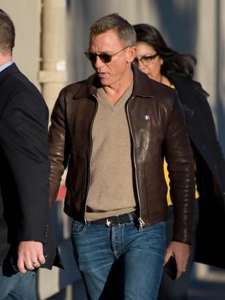 Как Daniel Craig носит Темно-коричневый кожаный бомбер, Светло-коричневый свитер с v-образным вырезом, Темно-синие джинсы, Черный кожаный плетеный ремень