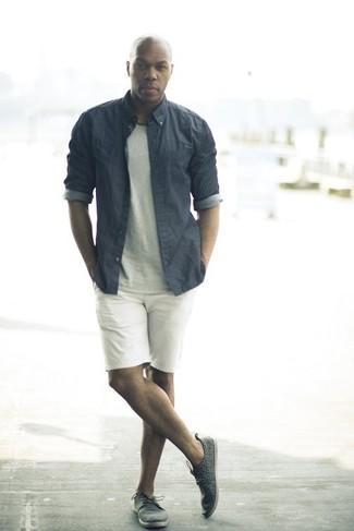 Серая классическая рубашка из шамбре: с чем носить и как сочетать мужчине: Если ты приписываешь себя к той немногочисленной категории парней, способных разбираться в том, что стильно, а что нет, тебе придется по вкусу дуэт серой классической рубашки из шамбре и белых шорт. Такой ансамбль несложно приспособить к повседневным условиям городской жизни, если надеть в паре с ним темно-серые кожаные низкие кеды.
