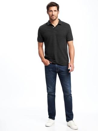 Темно-серая футболка-поло и темно-синие джинсы — прекрасный вариант простого, но стильного лука. Очень выигрышно здесь будут смотреться белые кожаные низкие кеды.