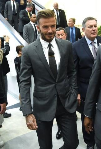 Темно-серый пиджак выглядит стильно в сочетании с черными классическими брюками.