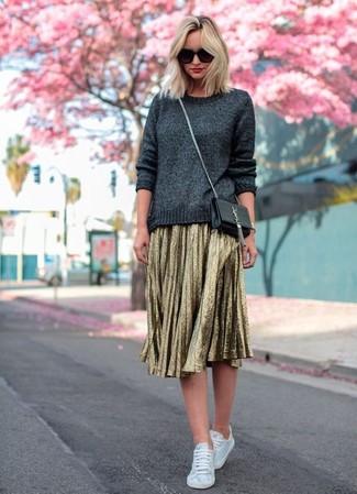 Как и с чем носить: темно-серый свитер с круглым вырезом, золотая юбка-миди со складками, белые низкие кеды из плотной ткани, черная кожаная сумка через плечо