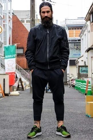 Темно-синий бомбер: с чем носить и как сочетать мужчине: Привлекательное сочетание темно-синего бомбера и темно-синих спортивных штанов позволит подчеркнуть твой личный стиль и выигрышно выделиться из общей массы. Зеленые кроссовки подарят комфорт в течение всего дня.