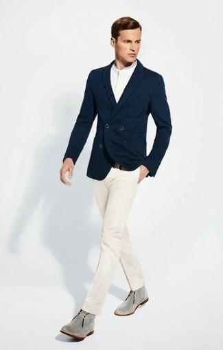 Несмотря на то, что это классический лук, образ из темно-синего двубортного пиджака и белых классических брюк приходится по вкусу джентльменам, покоряя при этом сердца прекрасных дам. Завершив образ серыми замшевыми ботинками дезертами, можно привнести в него динамичность.