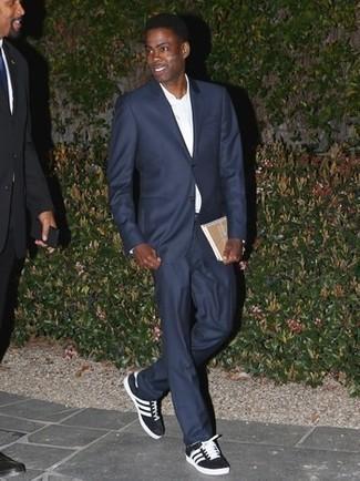 Как и с чем носить: темно-синий костюм, белая классическая рубашка, черно-белые низкие кеды из плотной ткани