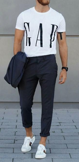 Как и с чем носить: темно-синий костюм, бело-черная футболка с круглым вырезом с принтом, белые кожаные низкие кеды, черные часы