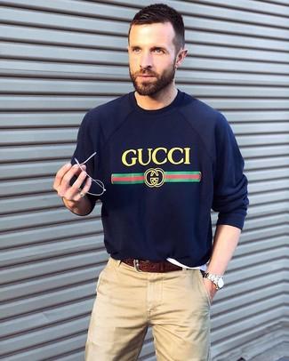 Как и с чем носить: темно-синий свитер с круглым вырезом с принтом, бежевые брюки чинос, темно-коричневый кожаный ремень, серебряные часы