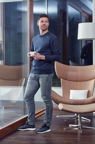 Темно-синий свитер с круглым вырезом: с чем носить и как сочетать мужчине: Темно-синий свитер с круглым вырезом в сочетании с серыми джинсами поможет выразить твою индивидуальность. Почему бы не привнести в этот образ немного легкости с помощью темно-синих кроссовок?