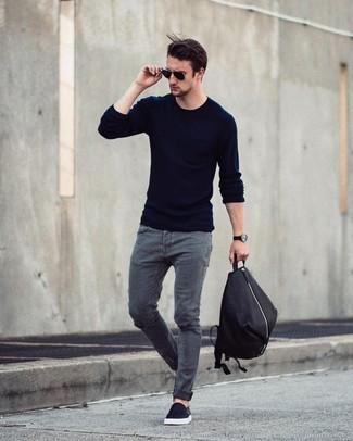 Как и с чем носить: темно-синий свитер с круглым вырезом, серые джинсы, черные слипоны, черный рюкзак