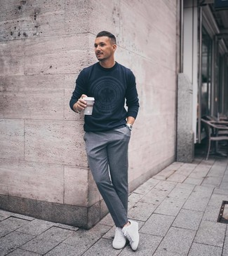 Как и с чем носить: темно-синий свитер с круглым вырезом с принтом, серые классические брюки, белые низкие кеды, серебряные часы