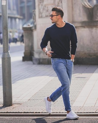 Как и с чем носить: темно-синий свитер с круглым вырезом, синие джинсы, белые низкие кеды