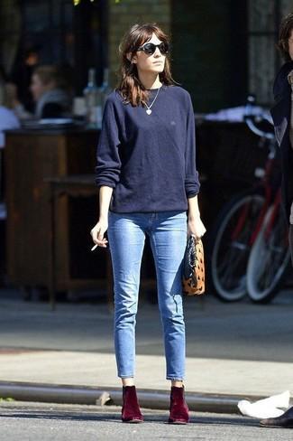 Как Alexa Chung носит Темно-синий свободный свитер, Голубые джинсы, Темно-красные бархатные ботильоны, Светло-коричневый замшевый клатч