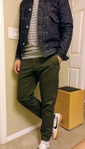 Темно-синяя джинсовая куртка: с чем носить и как сочетать мужчине: Дуэт темно-синей джинсовой куртки и оливковых брюк чинос поможет создать незаезженный мужской лук в повседневном стиле. Любишь экспериментировать? Заверши ансамбль бело-темно-синими кожаными низкими кедами.