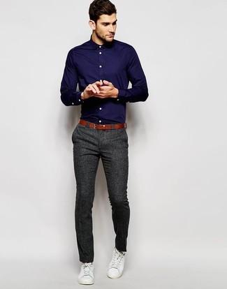 Темно-синяя классическая рубашка и темно-серые классические брюки — хороший пример элегантного мужского стиля. И почему бы не добавить в этот образ немного непринужденности с помощью белых низких кед?