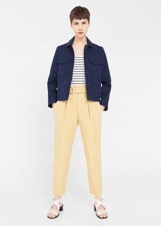 Как и с чем носить: темно-синяя куртка в стиле милитари, бело-черная футболка с круглым вырезом в горизонтальную полоску, желтые брюки-галифе, белые кожаные босоножки на каблуке