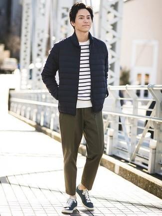 Модный лук: темно-синяя легкая куртка-пуховик, бело-темно-синяя футболка с круглым вырезом в горизонтальную полоску, оливковые брюки чинос, темно-сине-белые низкие кеды из плотной ткани