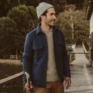 Как и с чем носить: темно-синяя шерстяная куртка-рубашка, бежевый свитер с круглым вырезом, светло-коричневые брюки чинос, серая шапка