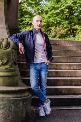 Как и с чем носить: темно-синяя куртка харрингтон, бежевая футболка с круглым вырезом, синие джинсы, белые кожаные низкие кеды