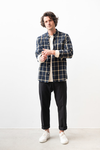 Как и с чем носить: темно-синяя фланелевая рубашка с длинным рукавом в клетку, белая лонгслив с горловиной на пуговицах, черные брюки чинос, белые кожаные низкие кеды