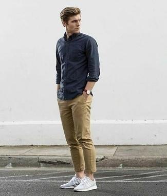 Темно-синяя рубашка с длинным рукавом: с чем носить и как сочетать мужчине: Несмотря на то, что это достаточно простой образ, дуэт темно-синей рубашки с длинным рукавом и светло-коричневых брюк чинос приходится по душе джентльменам, неизбежно покоряя при этом сердца прекрасных дам. Чтобы добавить в образ немного непринужденности , на ноги можно надеть серые кроссовки.