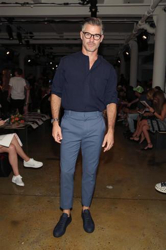 Как одеваться мужчине за 50: Сочетание темно-синей рубашки с длинным рукавом и синих брюк чинос позволит выглядеть аккуратно, но при этом выразить твой индивидуальный стиль. Чтобы привнести в образ толику легкой небрежности , на ноги можно надеть темно-синие кожаные низкие кеды.