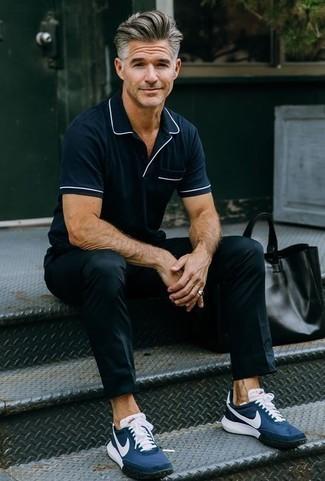 Модные мужские луки 2020 фото: Темно-синяя футболка-поло выглядит стильно в паре с черными брюками чинос. Ты можешь легко адаптировать такой ансамбль к повседневным условиям городской жизни, надев темно-синими кроссовками.