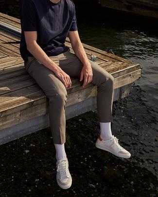 Бежевые брюки чинос: с чем носить и как сочетать: Темно-синяя футболка с круглым вырезом и бежевые брюки чинос — хороший вариант, если ты ищешь непринужденный, но в то же время стильный мужской образ. Вместе с этим луком выгодно смотрятся белые кожаные низкие кеды.