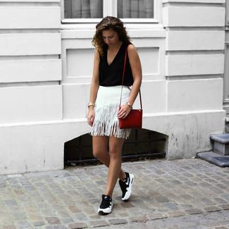 Как и с чем носить: черный топ без рукавов, белая мини-юбка c бахромой, черно-белые кроссовки, красная кожаная сумка через плечо