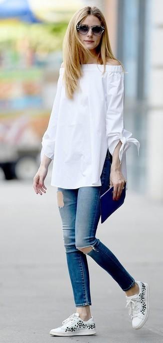 Как Olivia Palermo носит Белый топ с открытыми плечами, Синие рваные джинсы скинни, Белые низкие кеды с цветочным принтом, Синий кожаный клатч